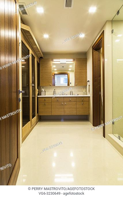 Basement bathroom with white marble floor, bamboo wood vanity and sauna room inside luxurious stained cedar and timber wood home