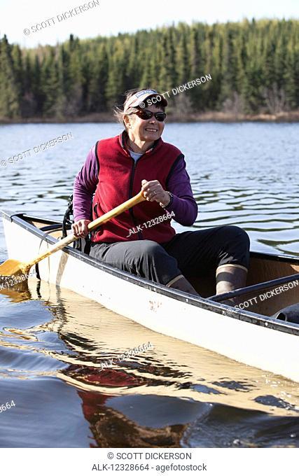 Woman steering a canoe in the Swanson Lake area, Kenai Peninsula, South-central Alaska; Alaska, United States of America