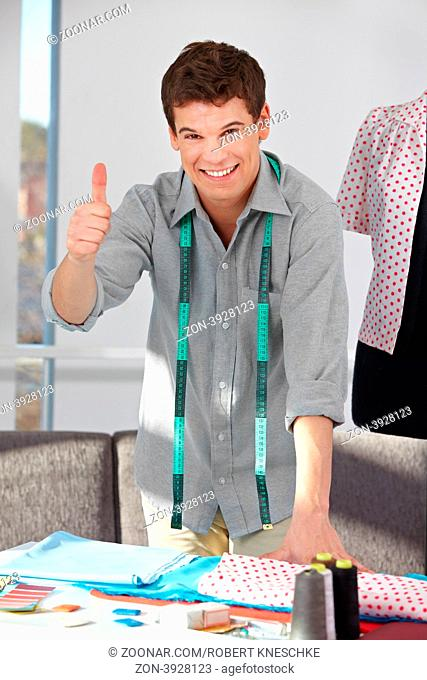 Lachender Modedesigner im Atelier hält seinen Daumen hoch