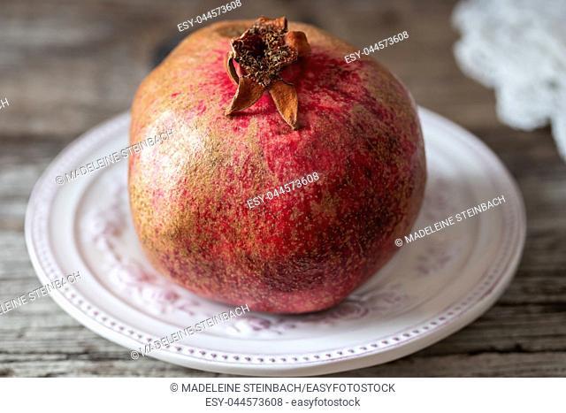 Fresh pomegranate on a vintage plate
