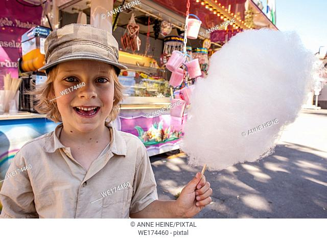 Boy happy to get candyfloss for the first time. Fair, Germany