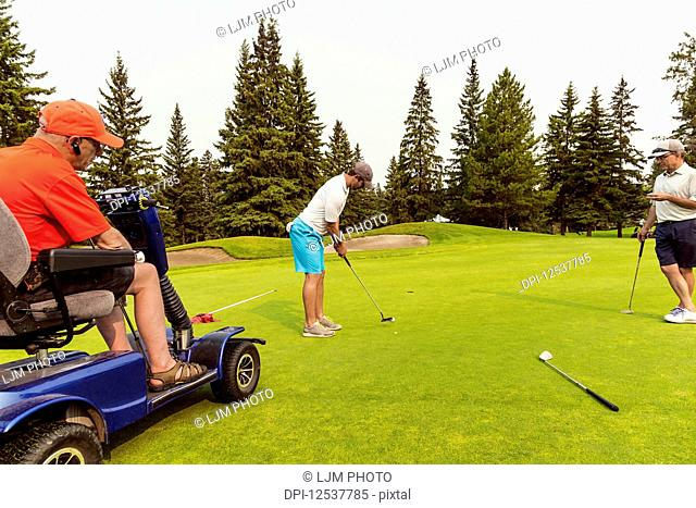 Two able bodied golfers team up with a disabled golfer using a specialized powered golf wheelchair and putting together on a golf green playing best ball;...