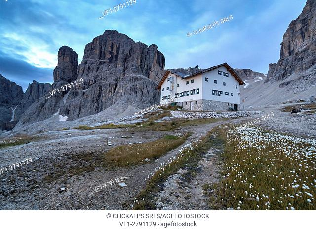 Europe, Italy, South Tyrol, Bolzano. Rifugio Franco Cavazza at Pisciadu in the Sella group with carpet of cotton grass in the foreground, Dolomites