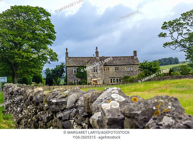 Scenic view of an old stone house in the countryside with stone wall, Yorkshire, England, UK
