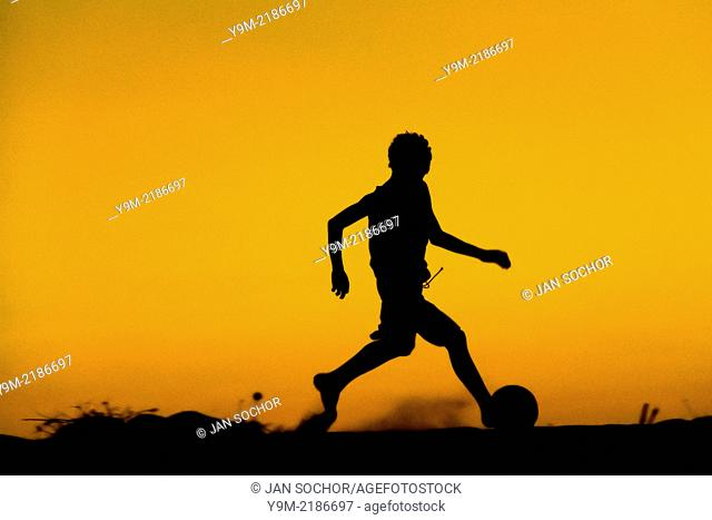 A young boy plays football during the sunset on the beach in Uruau, a small fishing community in the northeastern Brazil, 21 March 2004