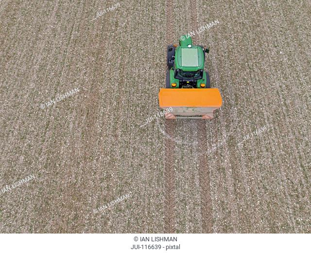 Aerial View Of Tractor Fertilizing Crop In Field