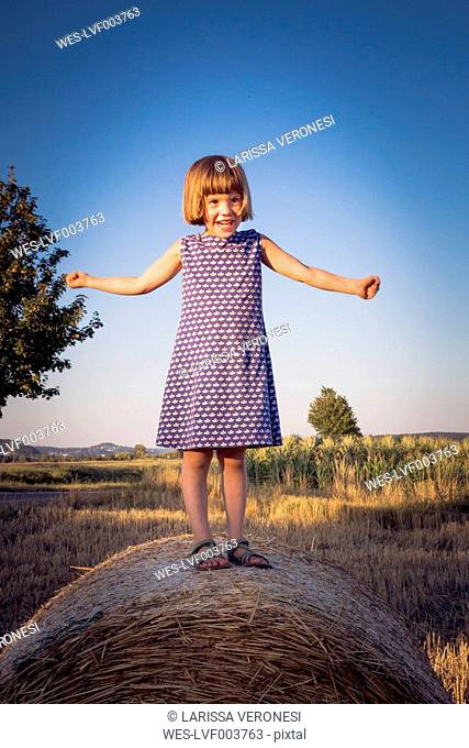 Portrait of little girl standing on straw bale with outstretched arms