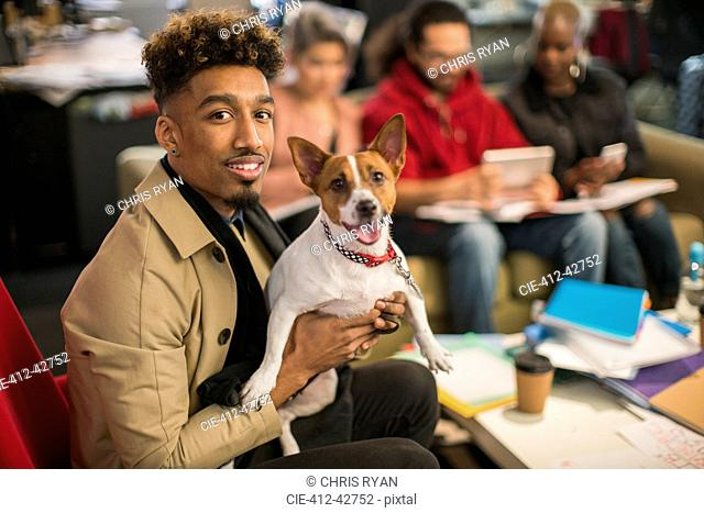 Portrait smiling creative businessman with dog in office