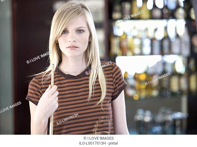 A teenage girl playing pool