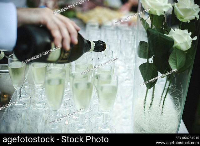 Waiter serving of sparkling white wine