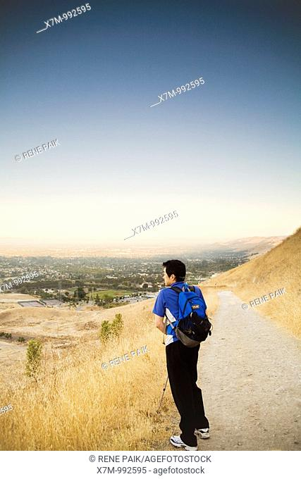 Shortly after sunrise, a male Korean hiker looks down at the view of the city of Fremont and Ohlone College from the Peak Trail at Mission Peak Regional...