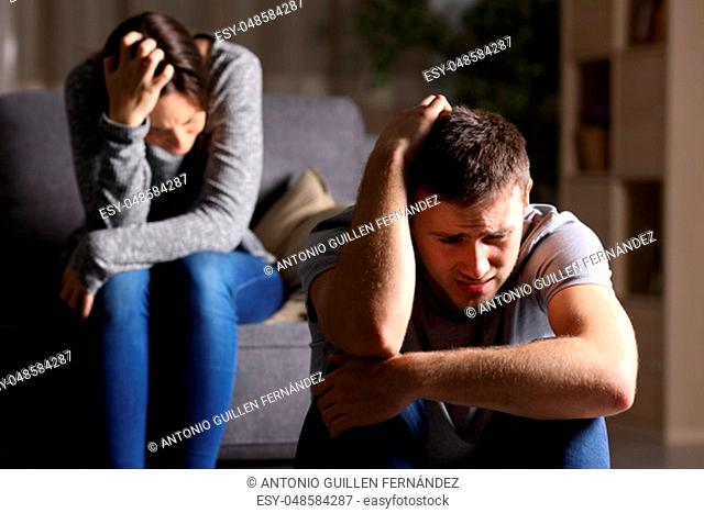 Sad couple after breaking up sitting on a couch in the living room in a house indoor with a dark background