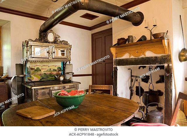 Kitchen room with antique cast iron Chapleau stove and wooden dining table inside an old Canadiana (1840s) fieldstone cottage style residential house, Quebec