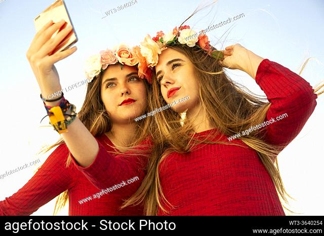 Two young girls with red dress and long blonde hair and roses taking a selfie