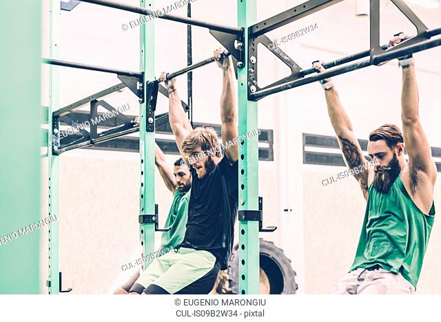 Three male cross trainers training on exercise bar in gym