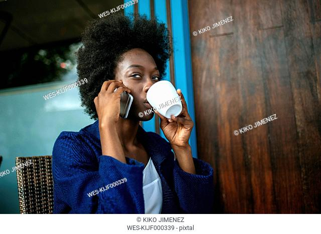 Portrait of young woman talking on mobile phone while drinking coffee in a street cafe