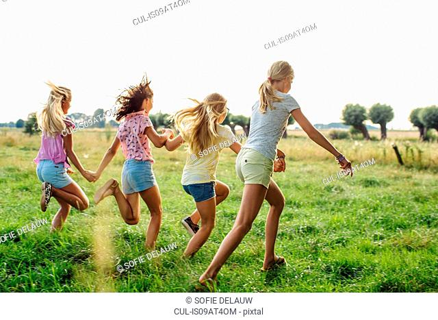 Girls holding hands, running in line, on field, Flanders, Belgium