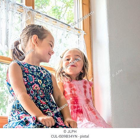 Girl sitting on windowsill smiling