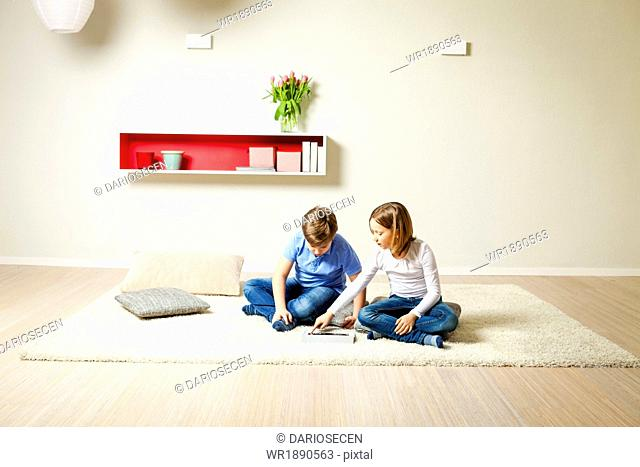 Children using tablet computer at home, Munich, Bavaria, Germany