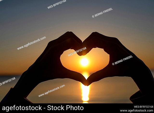 Germany, Mecklenburg-West Pomerania, Poel Island, Silhouette of hands making heart shape by sea at sunset