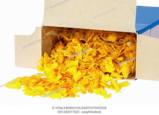 Corn flakes spill out of cardboard box isolated on white background