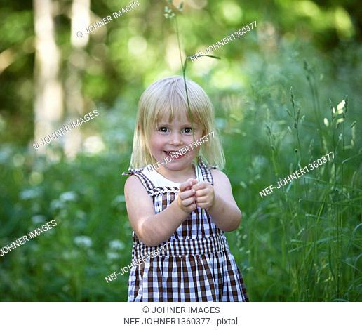 Portrait of smiling girl holding grass on meadow