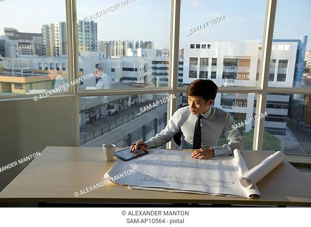 Singapore, Architect sitting at table with architectural plans and digital tablet