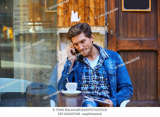 Young man with smartphone in an cafe outdoor sitting