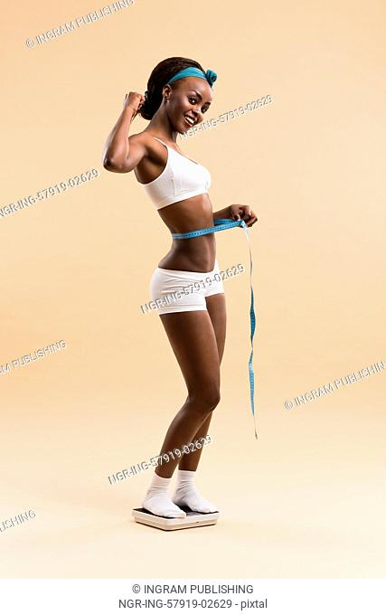 African woman standing on scale measuring waist with tape celebrating weightloss and a healthy fit body