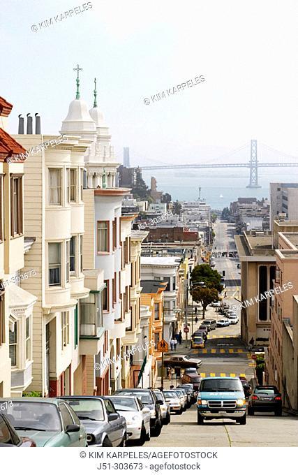 Steep, hilly street, Oakland Bay Bridge in distance. San Francisco. California, USA
