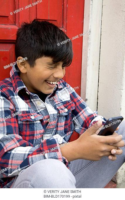 Asian boy using cell phone at door