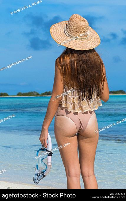 Young woman with wet skin and with a snorkel standing on sand and going to swim in clear sea