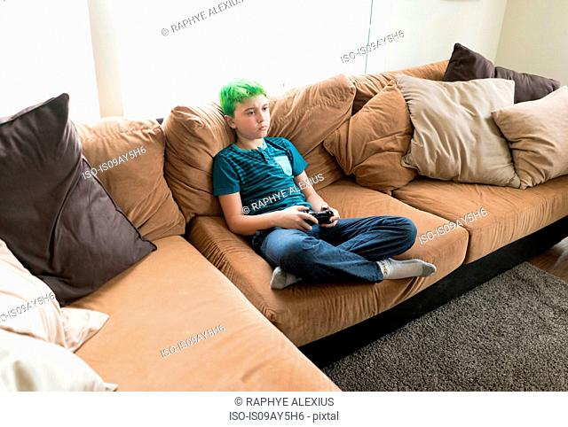 Boy playing video game on sofa