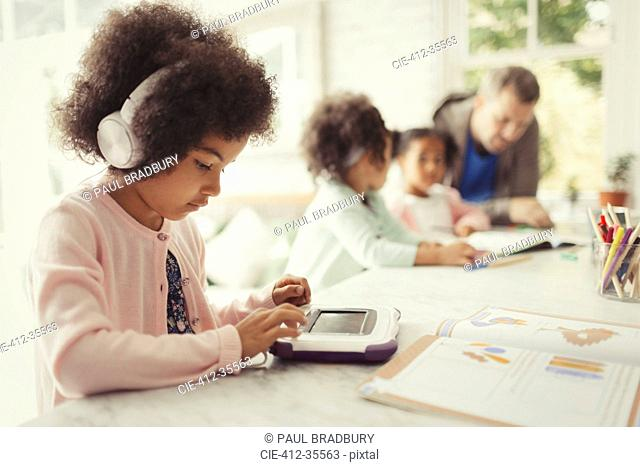 Girl with headphones using digital tablet doing homework at table