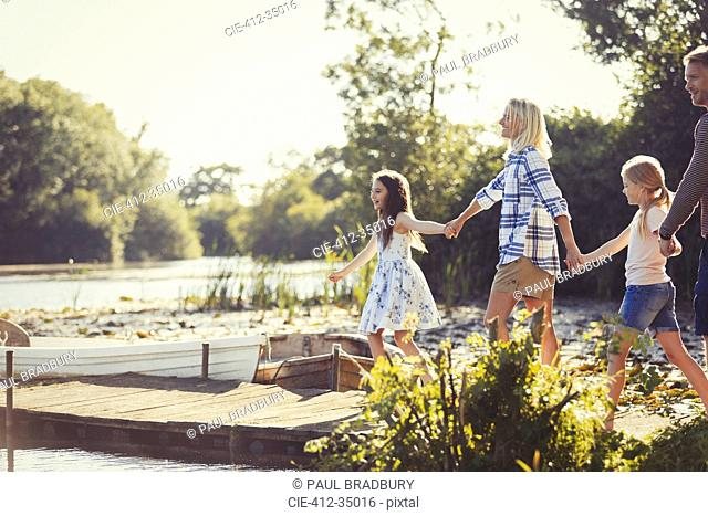 Family holding hands and walking on sunny lakeside dock