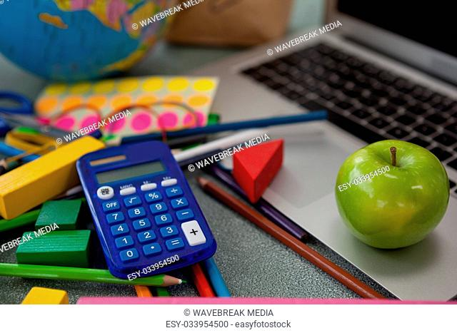 Various school supplies, apple and laptop on chalkboard