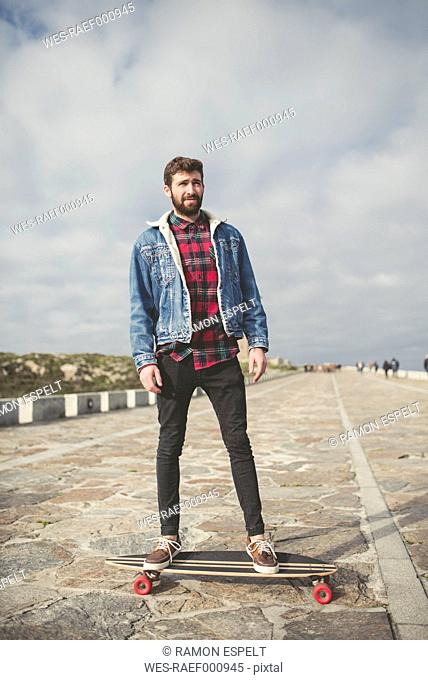 Spain, A Coruna, portrait of young man standing on his longboard