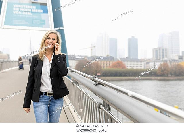 Businesswoman phoning on a bridge