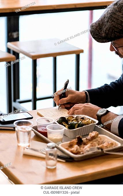 Businessman writing notes over lunch of grilled chicken and vegetables in restaurant