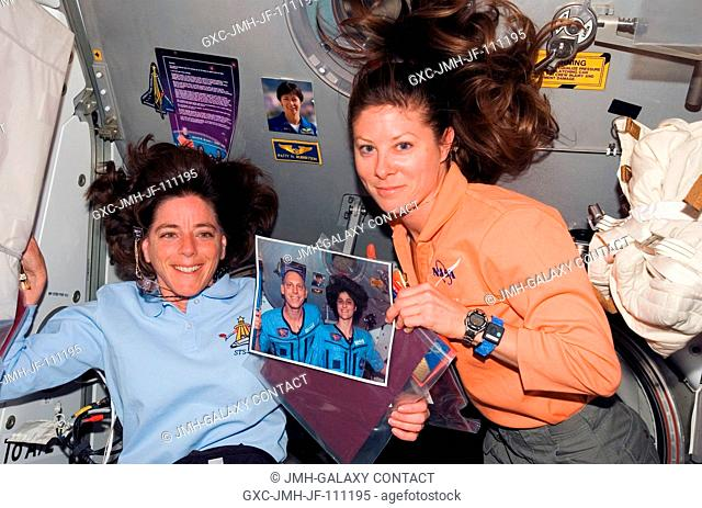 Astronauts Barbara R. Morgan (left) and Tracy Caldwell, both STS-118 mission specialists, pose with a photo of astronauts Clay Anderson and Sunita Williams