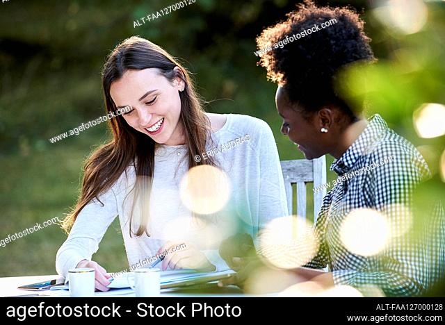 Smiling young friends studying at table in park