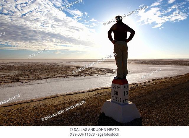 Africa, Tunisia, Chott El Jerid, Flat Dry Salt Lake between Tozeur and Kebili, Man Standing on Signpost