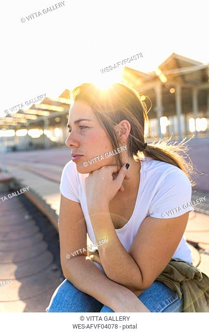 Portrait of young woman at backlight looking at distance