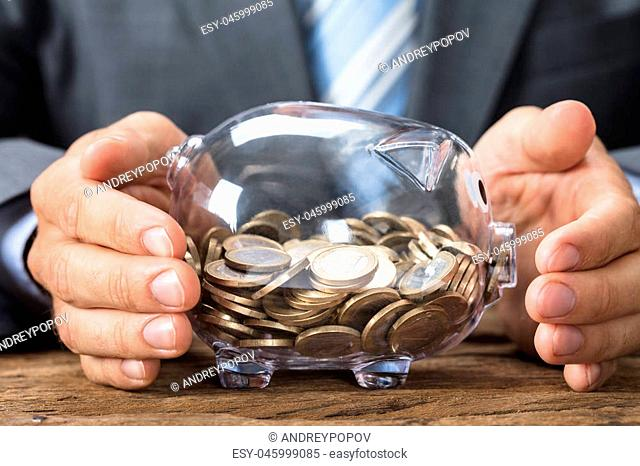 Closeup of businessman covering transparent piggy bank with coins on table