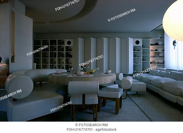 White leather banquette seating around circular table in white living room with white sofa and folding screen