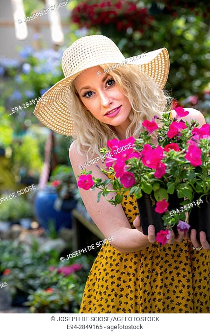 A happy 30 year old blond woman shopping in a plant nursery holding potted petunias