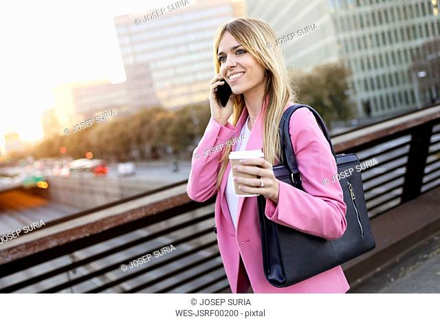 Young businesswoman using smartphone and holding coffee to go