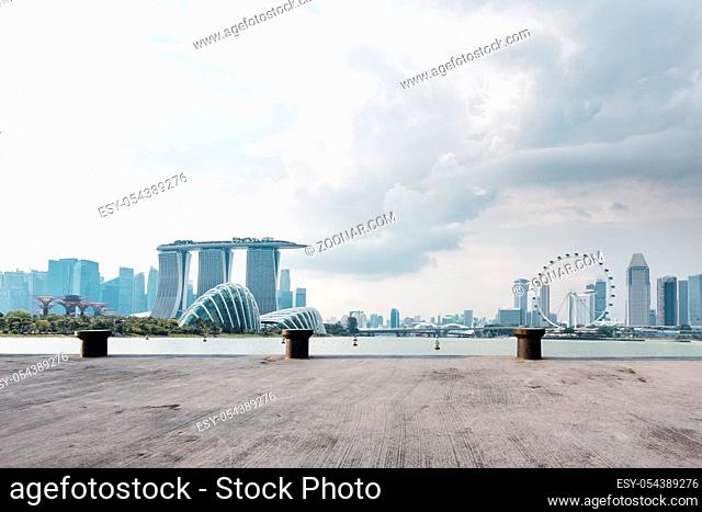 empty concrete floor and cityscape of singapore in cloud sky