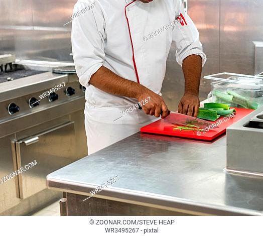 Chef cutting leeks in commercial stainless steel kitchen in restaurant