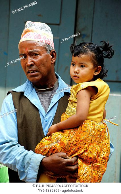 nepalis man holding his grand daughter , street life in kathmandu , nepal
